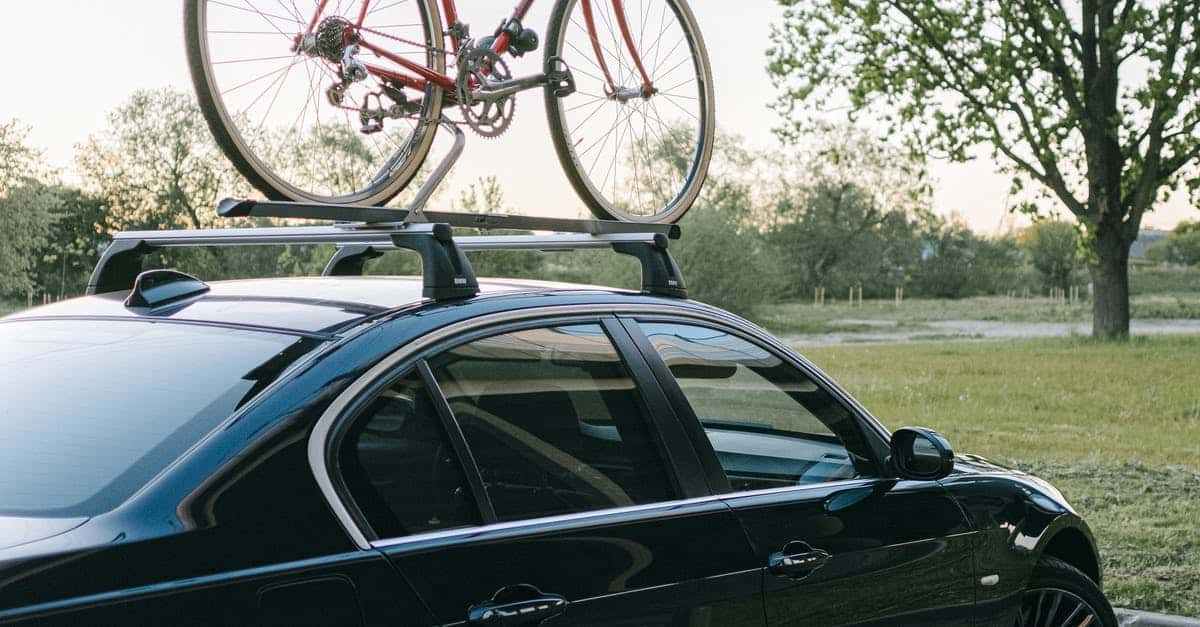 A bicycle parked on the side of a car