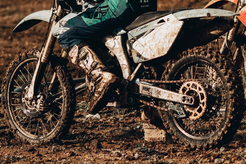 A motorcycle parked on the side of a dirt field