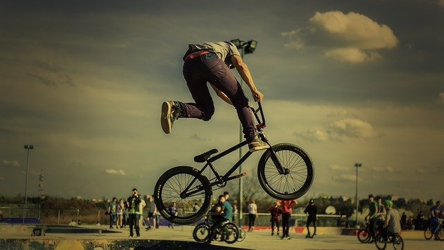 A man doing a trick on a bicycle jumping in the air