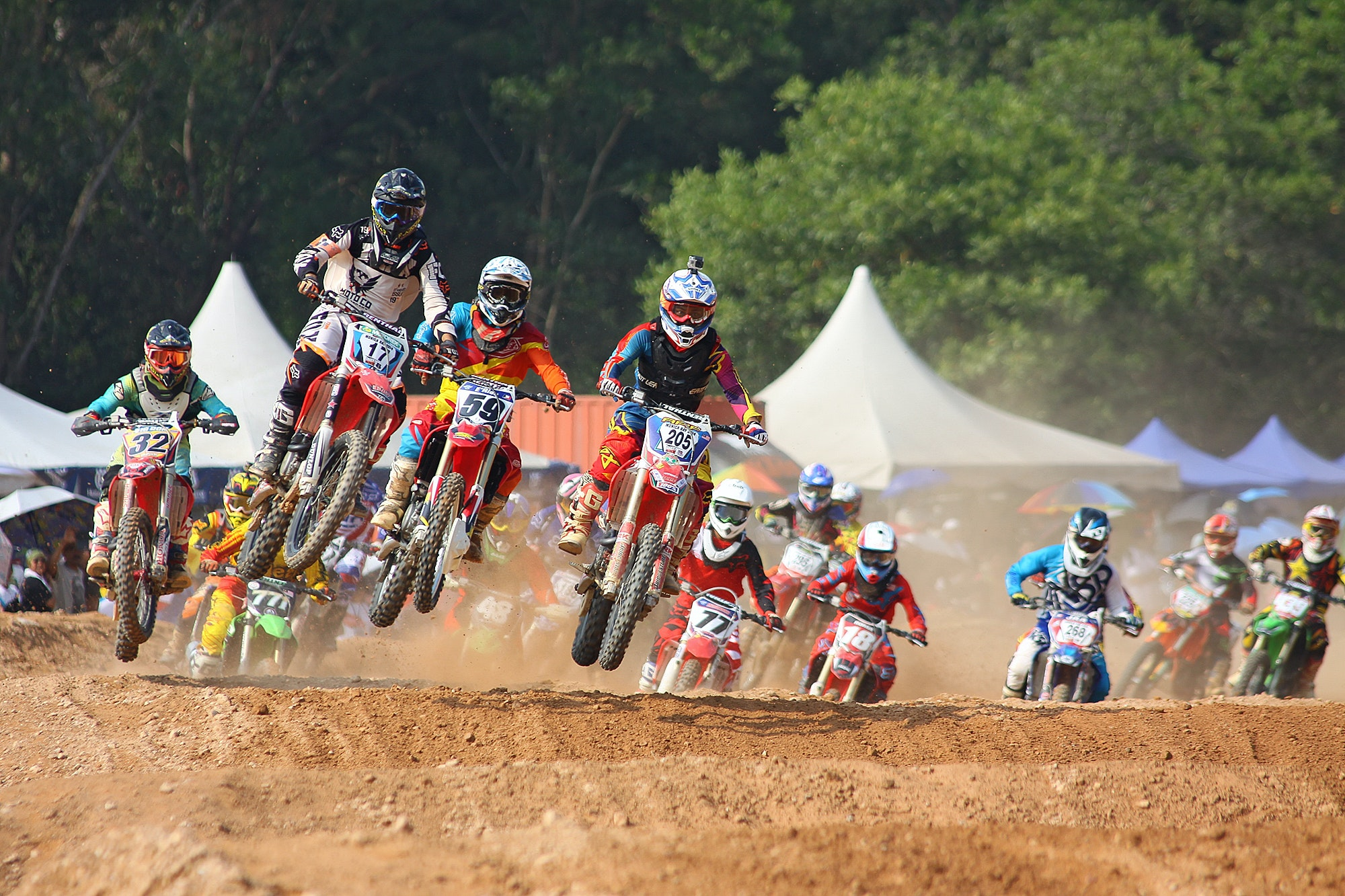 A group of people racing each other on a dirt road