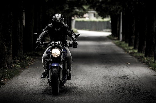 A person riding a motorcycle down a street